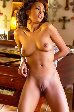 Noel Monique strips near the piano